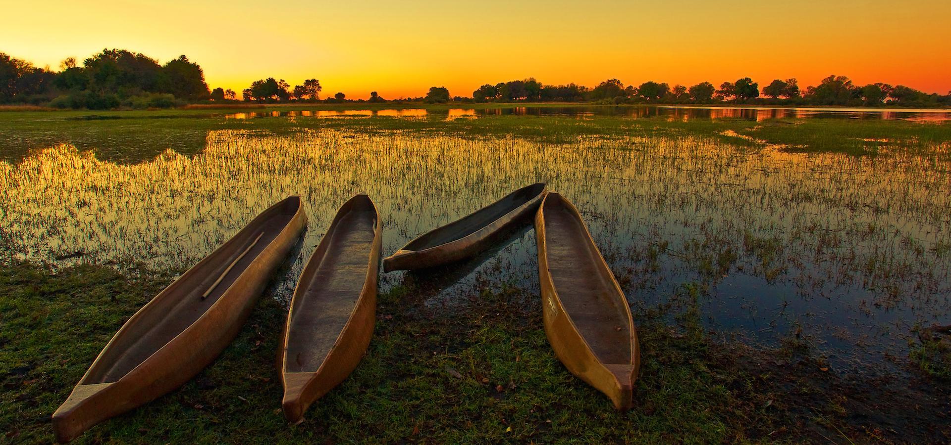 Sonnenaufgang im Okavango Delta: Im Vordergrund drei Mokoro, das klassische Fortbewegungsmittel im größten Binnendelta der Welt